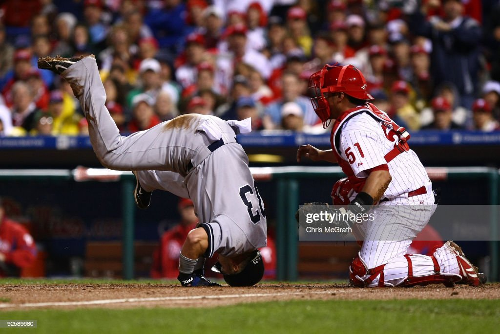 Nick Swisher of the New York Yankees collides with Carlos Ruiz of the Philadelphia Phillies as he scores in the top of the fifth inning in Game Three...