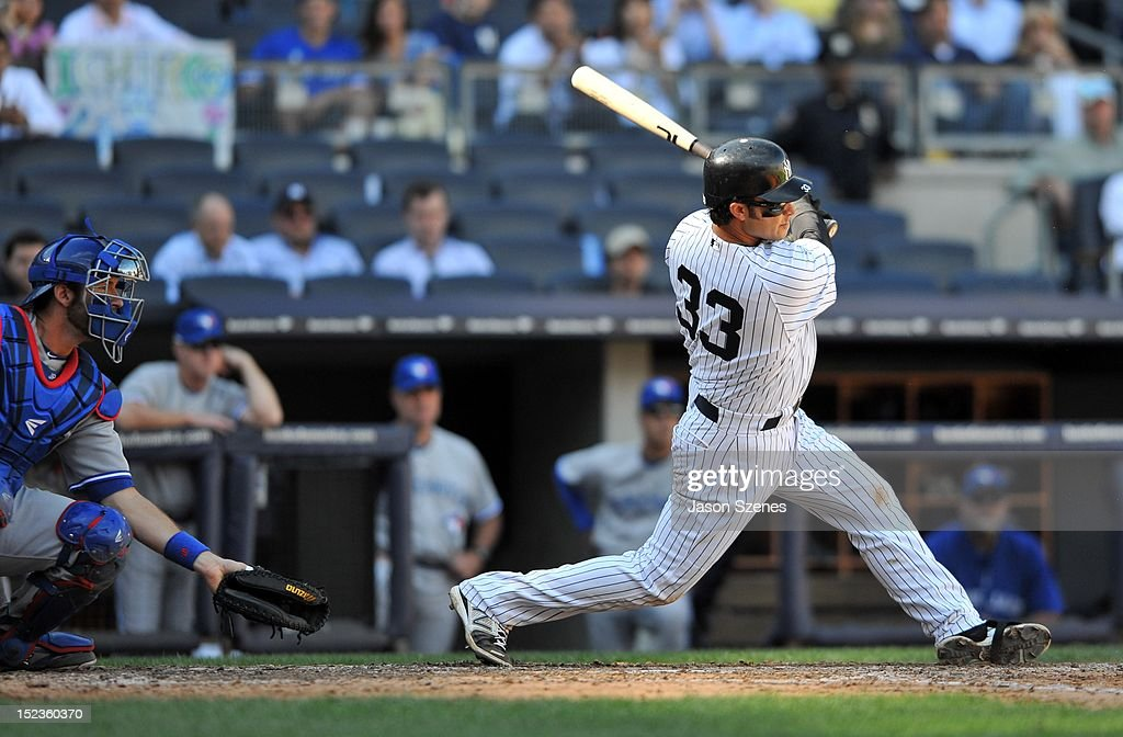 <a gi-track='captionPersonalityLinkClicked' href=/galleries/search?phrase=Nick+Swisher&family=editorial&specificpeople=206417 ng-click='$event.stopPropagation()'>Nick Swisher</a> #33 of the New York Yankees (R) connects on an RBI single in the ninth inning against the Toronto Blue Jays during the first game of a double header at Yankee Stadium on September 19, 2012 in the Bronx borough of New York City.