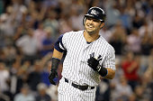 Nick Swisher of the New York Yankees smiles at his dugout as he runs the bases after his third inning grand slam against the Texas Rangers at Yankee...