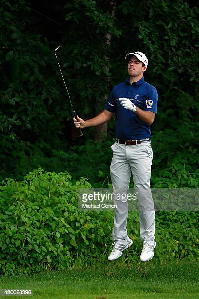 Nick Taylor jumps in the air to get a view of the 10th hole as he lines up his third shot during the first round of the John Deere Classic held at...