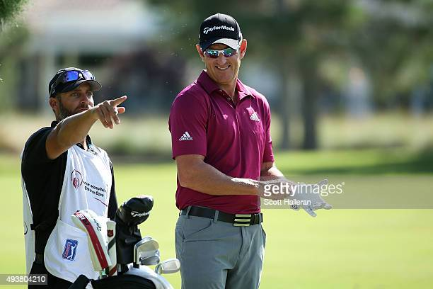 Nick Taylor of Canada and his caqddie prepare to play a shot on the ninth hole during the first round of the Shriners Hospitals For Children Open on...