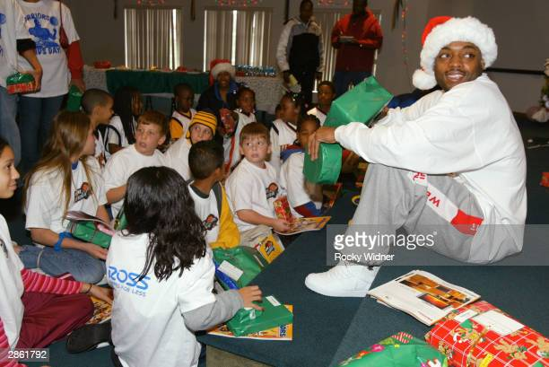 Nick Van Exel of the Golden State Warriors passes out gifts as he sits with kids at the Faith Fellowship Foursquare Church on December 24 2003 in...