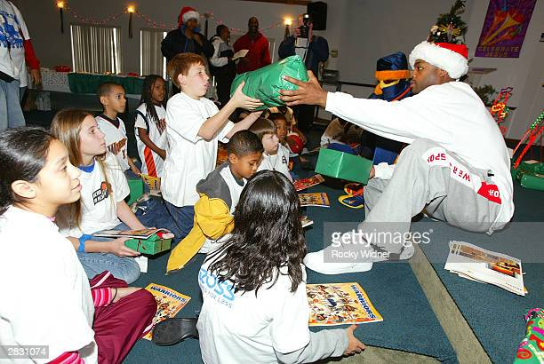 Nick Van Exel of the Golden State Warriors passes out gifts to children at the Faith Fellowship Foursquare Church on December 24 2003 in Oakland...