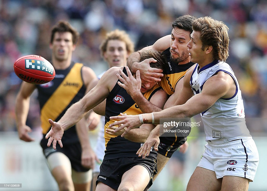Nick Vlastuin of the Tigers gets his head ripped off by teamate Troy Chaplin who contests for the ball against Matt de Boer of the Dockers during the round 17 AFL match between the Richmond Tigers and the Fremantle Dockers at Melbourne Cricket Ground on July 21, 2013 in Melbourne, Australia.