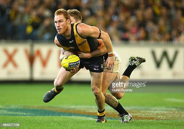 Nick Vlastuin of the Tigers handballs whilst being tackled by Dayne Beams of the Magpies during the round four AFL match between the Richmond Tigers...