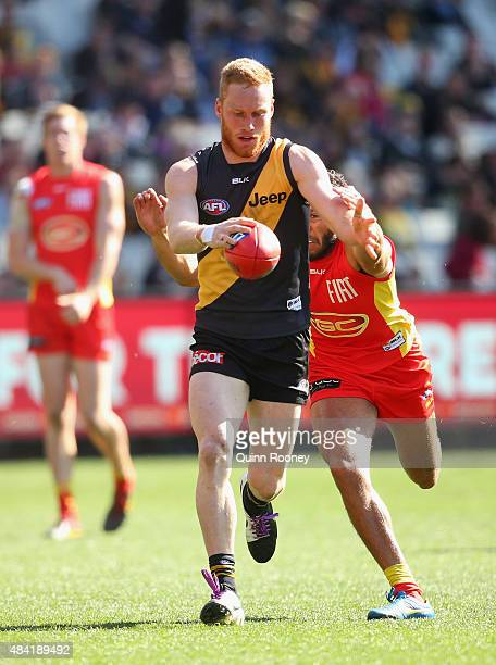 Nick Vlastuin of the Tigers kicks whilst being tackled by Harley Bennell of the Suns during the round 20 AFL match between the Richmond Tigers and...