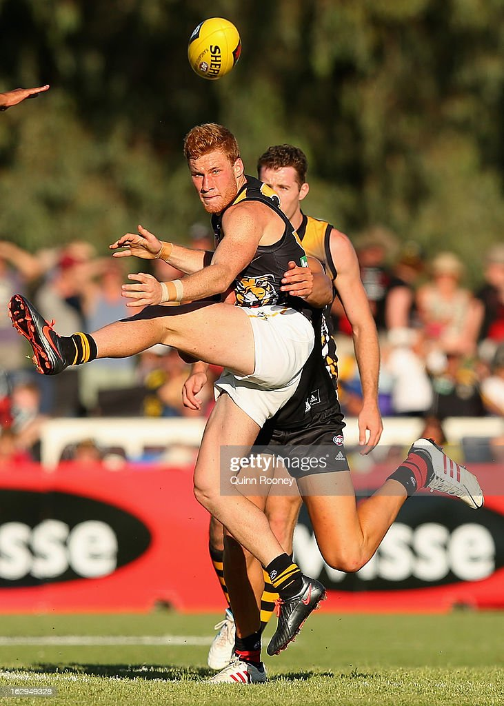 Nick Vlastuin of the Tigers kicks whilst being tackled during the round two AFL NAB Cup match between the Essendon Bombers and the Richmond Tigers at Wangaratta Showgrounds on March 2, 2013 in Wangaratta, Australia.