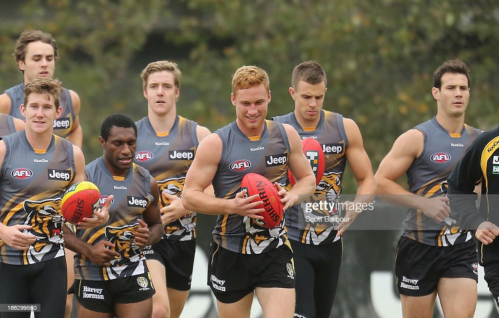 Nick Vlastuin (C) of the Tigers runs with the ball during a Richmond Tigers AFL Training session at ME Bank Centre on April 11, 2013 in Melbourne, Australia.