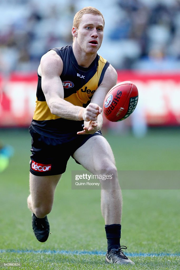 Nick Vlaustin of the Tigers handballs during the round 14 AFL match between the Richmond Tigers and the Brisbane Lions at Melbourne Cricket Ground on June 25, 2016 in Melbourne, Australia.
