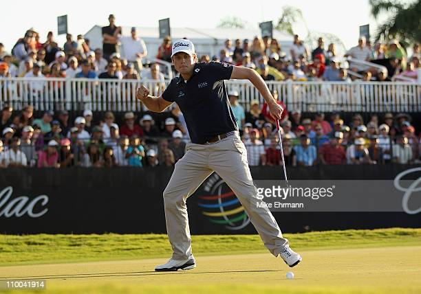 Nick Watney celebrates his birdie putt on the 18th green during the final round of the 2011 WGC Cadillac Championship at the TPC Blue Monster at the...