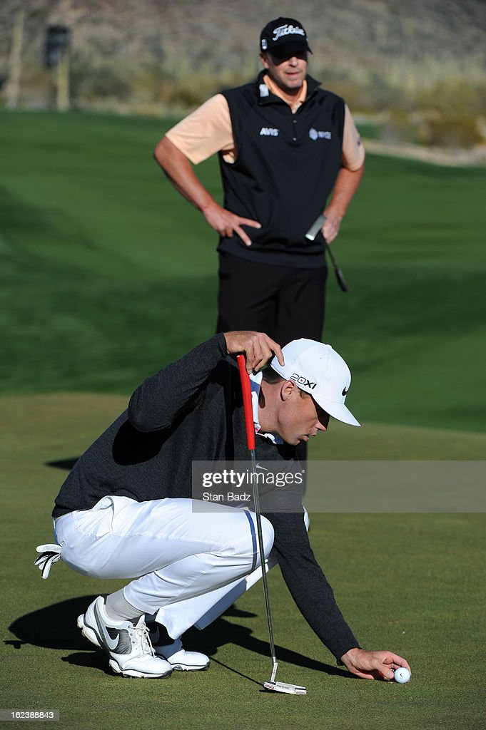 Nick Watney lines his ball as Steve Stricker waits to play the second hole during the second round of the World Golf Championships-Accenture Match Play Championship at The Golf Club at Dove Mountain on February 22, 2013 in Marana, Arizona.