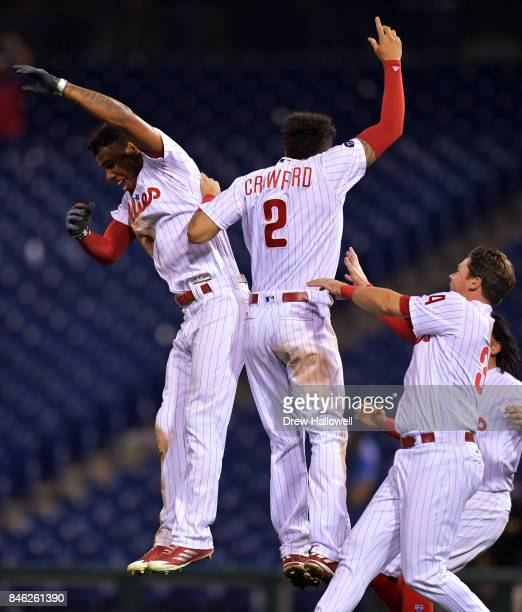 Nick Williams JP Crawford and Andrew Knapp of the Philadelphia Phillies celebrate William's walk off RBI double in the 15th inning against the Miami...