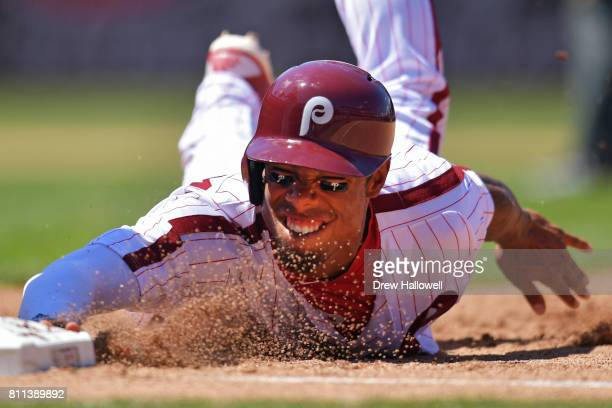 Nick Williams of the Philadelphia Phillies slides into first base on a pick off play in the fourth inning against the San Diego Padres at Citizens...