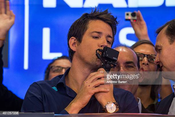 Nick Woodman founder and CEO of GoPro kisses a GoPro during the company's initial public offering at the Nasdaq Stock Exchange on June 26 2014 in New...