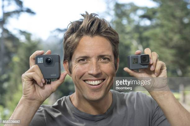 Nick Woodman founder and chief executive officer of GoPro Inc displays the Fusion 360 left and the Hero 6 cameras while standing for a photograph...