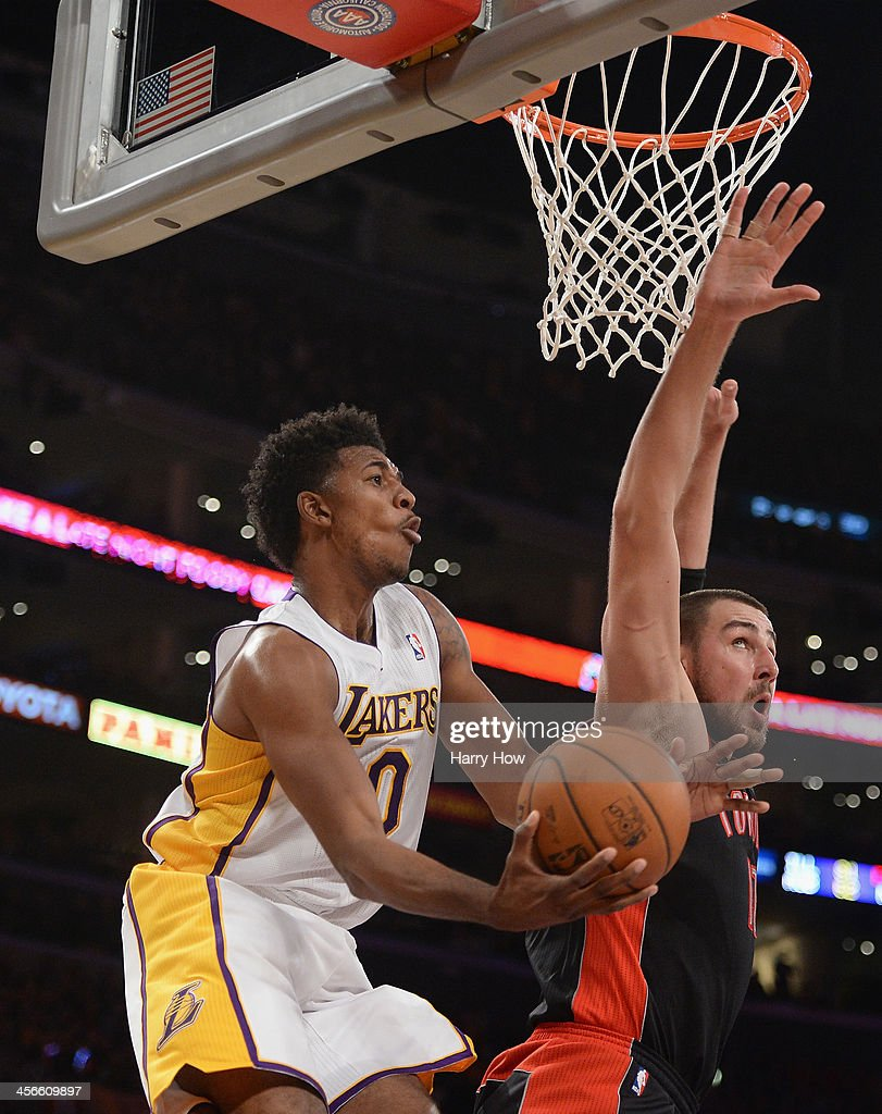 Nick Young #0 of the Los Angeles Lakers attempts a layup in front of <a gi-track='captionPersonalityLinkClicked' href=/galleries/search?phrase=Jonas+Valanciunas&family=editorial&specificpeople=5654195 ng-click='$event.stopPropagation()'>Jonas Valanciunas</a> #17 of the Toronto Raptors at Staples Center on December 8, 2013 in Los Angeles, California.
