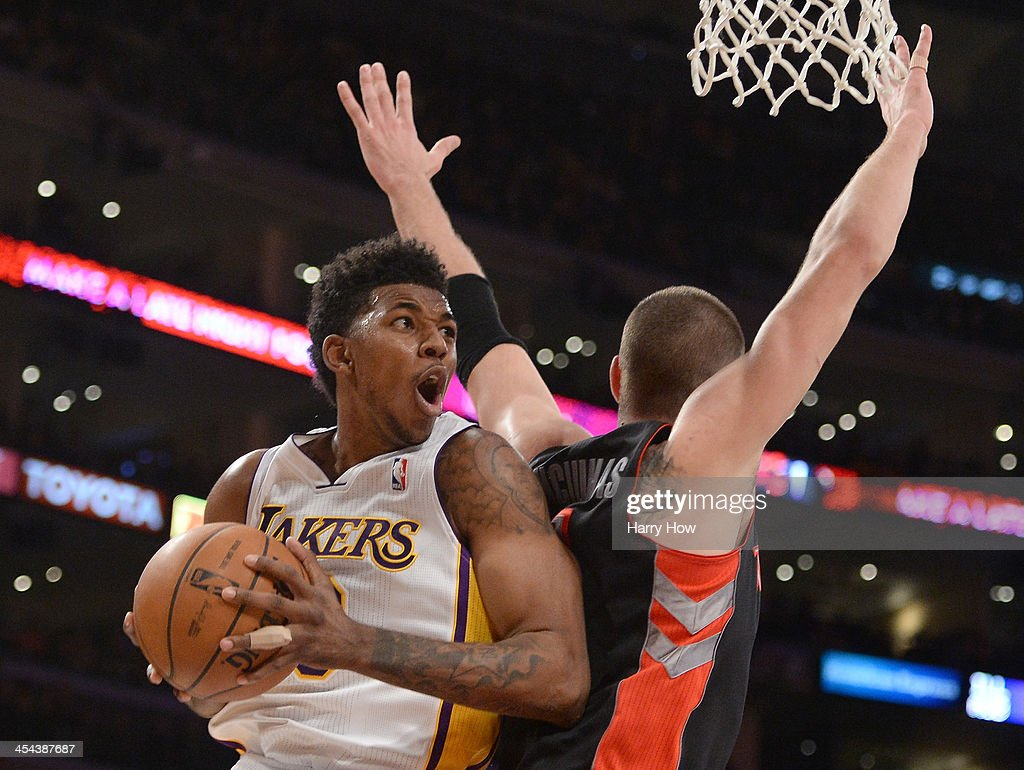Nick Young #0 of the Los Angeles Lakers attempts a shot off a spin move behind Jonas Valanciunas #17 of the Toronto Raptors during a 116-94 loss to the Raptors at Staples Center on December 8, 2013 in Los Angeles, California.