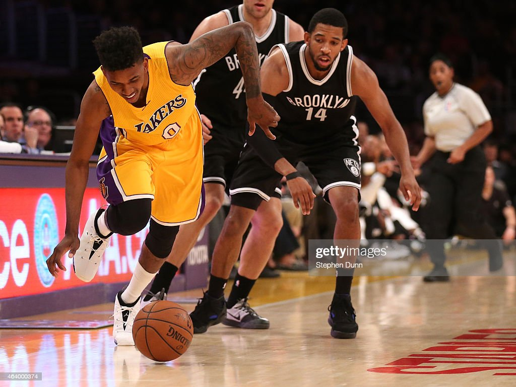 Nick Young of the Los Angeles Lakers goes for a loose ball against Darius Morris of the Brooklyn Nets at Staples Center on February 20 2015 in Los...