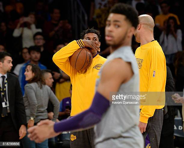 Nick Young of the Los Angeles Lakers speaks with teammate Robert Sacre as D'Angelo Russell warms up before the start of the basketball game between...