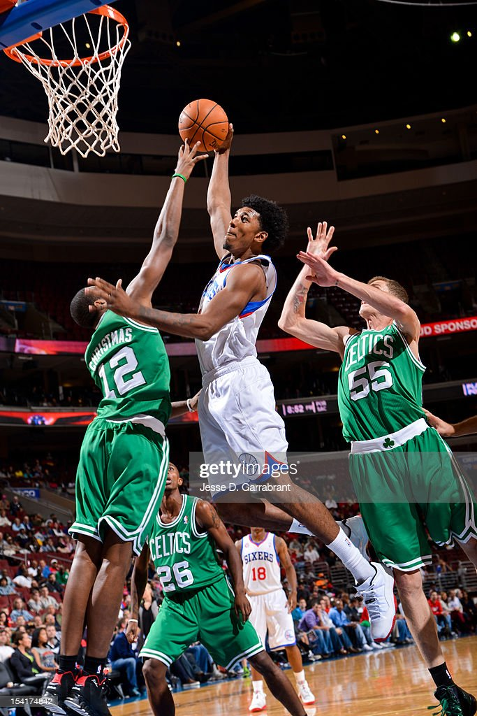 Nick Young #1 of the Philadelphia 76ers goes to the basket against Dionte Christmas #12 and Micah Downs #55 of the Boston Celtics during a pre-season game at the Wells Fargo Center on October 15, 2012 in Philadelphia, Pennsylvania.