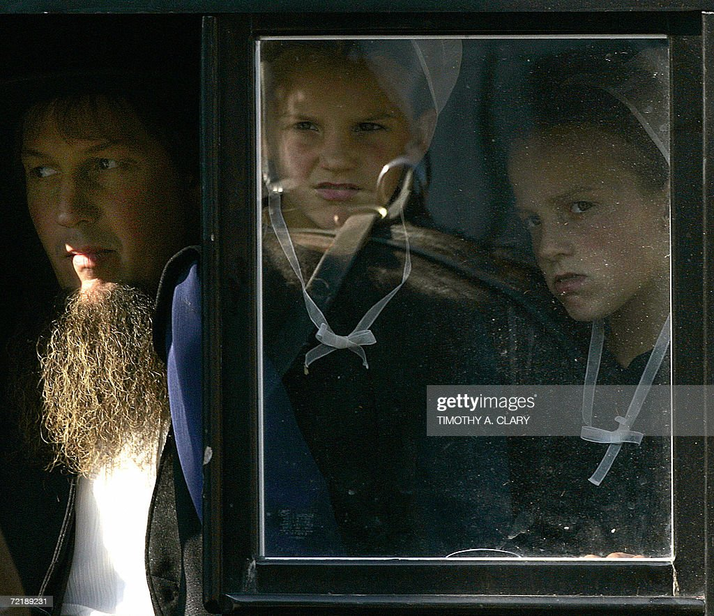 Amish girls peer out the window of a buggy during the funeral procession of Marian Fisher age 13 a victim of the Amish school shooting in Nickel...