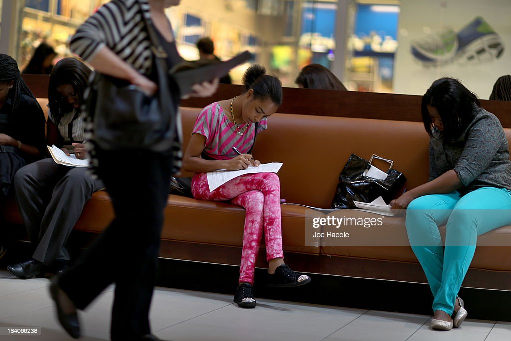 Nickiesha Watkis (C) fills out a job application form as she and others apply for jobs during a job fair at Sawgrass Mills on October 11, 2013 in Sunrise, Florida. As the holiday season approaches many of the roughly 50 retailers at the job fair including Banana Republic, J.Crew Factory, Victoria's Secret and Calvin Klein are starting to hire people for seasonal work as well as continuing to look for qualified full time employees.