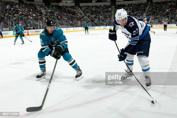 Nicklaj Ehlers of the Winnipeg Jets keeps the puck away from Brenden Dillon of the San Jose Sharks at SAP Center on November 25 2017 in San Jose...