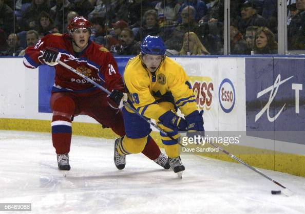 Nicklas Backstrom of Team Sweden carries the puck as he is hooked by Gennady Churilov of Team Russia during their World Jr Hockey Championship game...