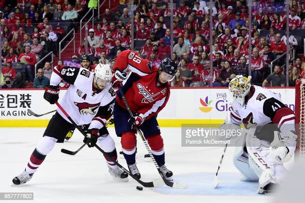 Nicklas Backstrom of the Washington Capitals and Oliver EkmanLarsson of the Arizona Coyotes battle for the puck in front of the net in the first...