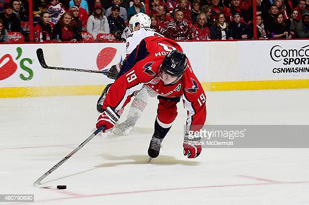 Nicklas Backstrom of the Washington Capitals battles for the puck against Milan Michalek of the Ottawa Senators in the first period during an NHL...