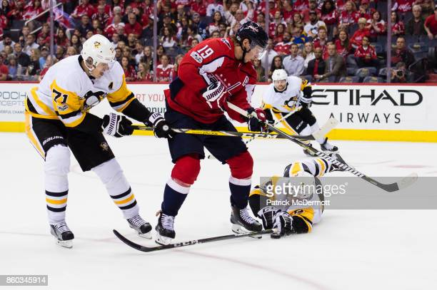 Nicklas Backstrom of the Washington Capitals battles for the puck against Evgeni Malkin and Chad Ruhwedel of the Pittsburgh Penguins in the third...