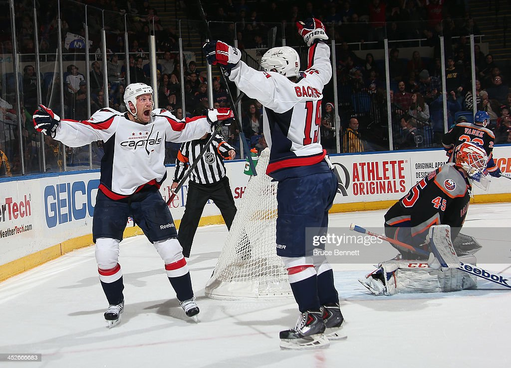 Nicklas Backstrom #19 of the Washington Capitals (R) celebrates his game tying shorthanded goal against Anders Nilsson #45 of the New York Islanders at 19:11 of the third period and is joined by <a gi-track='captionPersonalityLinkClicked' href=/galleries/search?phrase=Jason+Chimera&family=editorial&specificpeople=211264 ng-click='$event.stopPropagation()'>Jason Chimera</a> #25 (L) at the Nassau Veterans Memorial Coliseum on November 30, 2013 in Uniondale, New York. The Capitals defeated the Islanders 3-2 in overtime.