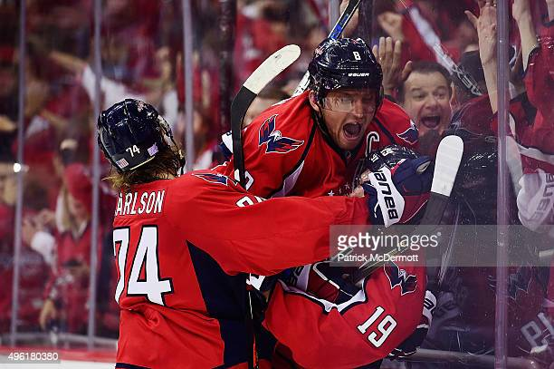 Nicklas Backstrom of the Washington Capitals celebrates with his teammates Alex Ovechkin and John Carlson after scoring a goal in the third period...