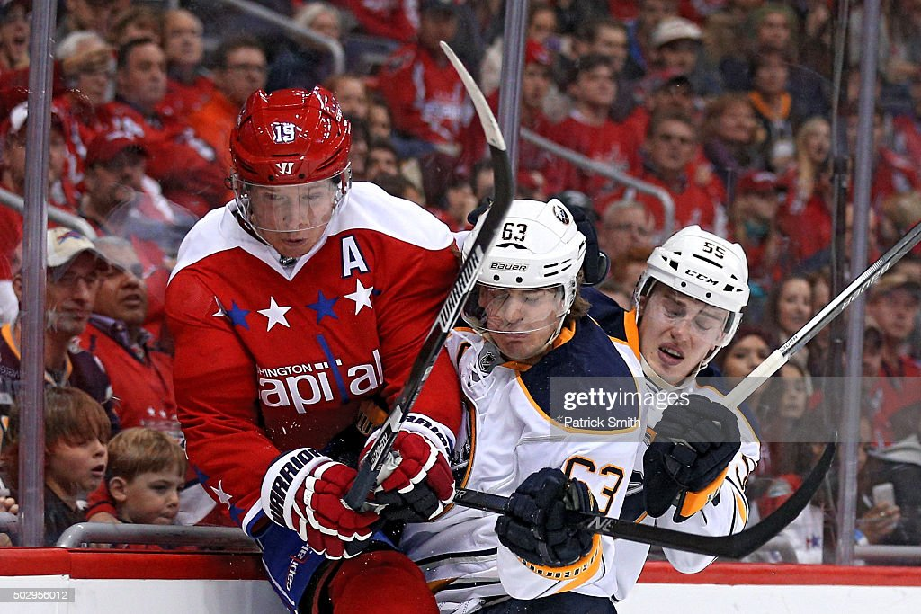 Nicklas Backstrom #19 of the Washington Capitals is bodychecked by Tyler Ennis #63 of the Buffalo Sabres during the second period at Verizon Center on December 30, 2015 in Washington, DC.