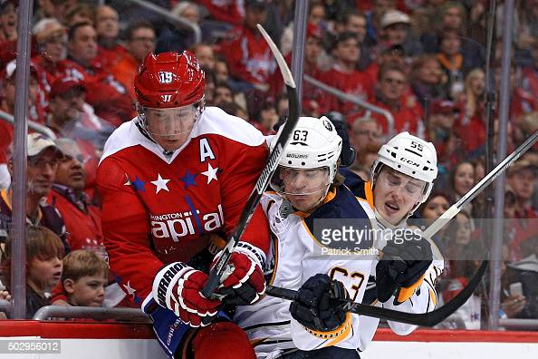 Nicklas Backstrom of the Washington Capitals is bodychecked by Tyler Ennis of the Buffalo Sabres during the second period at Verizon Center on...
