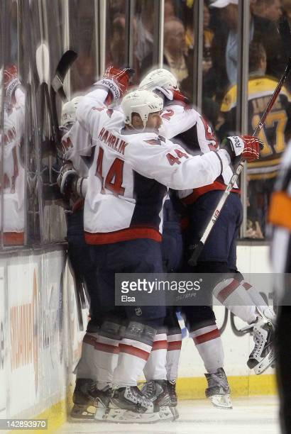 Nicklas Backstrom of the Washington Capitals is surrounded by teammates Roman Hamrlik and Mike Green after Backstrom scored the game winner in...
