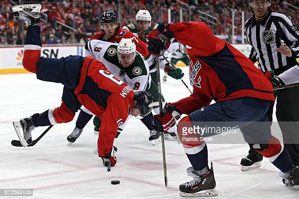 Nicklas Backstrom of the Washington Capitals is upended by Mikko Koivu of the Minnesota Wild during the third period at Verizon Center on February 26...