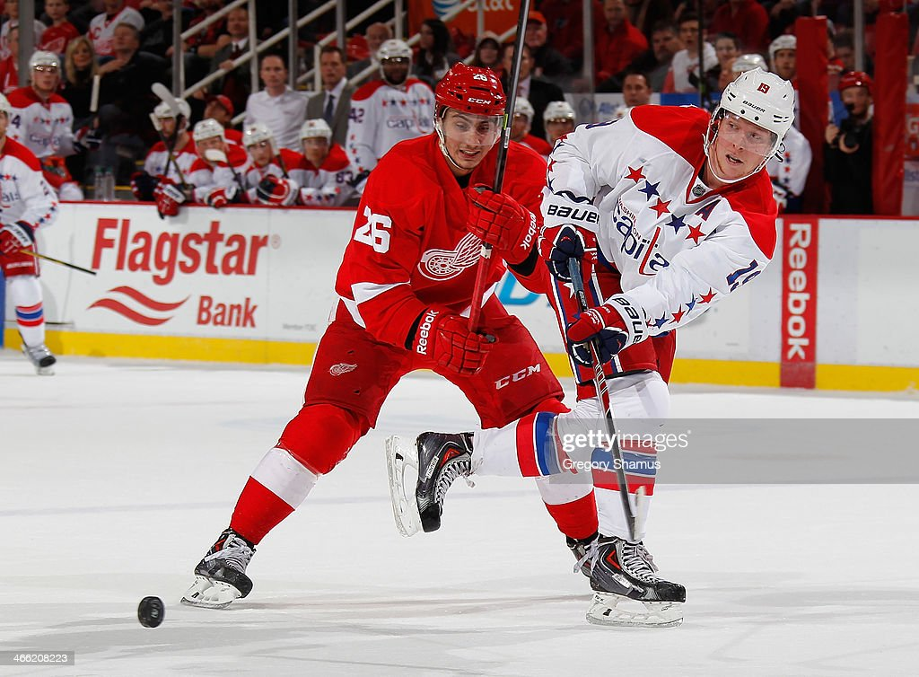 Nicklas Backstrom #19 of the Washington Capitals passes around Tomas Jurco #26 of the Detroit Red Wings during overtime at Joe Louis Arena on January 31, 2014 in Detroit, Michigan. Detroit won in a 4-3 in a shootout.