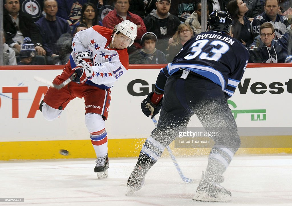 Nicklas Backstrom #19 of the Washington Capitals takes a shot on goal as <a gi-track='captionPersonalityLinkClicked' href=/galleries/search?phrase=Dustin+Byfuglien&family=editorial&specificpeople=672505 ng-click='$event.stopPropagation()'>Dustin Byfuglien</a> #33 of the Winnipeg Jets defends during third-period action at the MTS Centre on March 21, 2013 in Winnipeg, Manitoba, Canada.