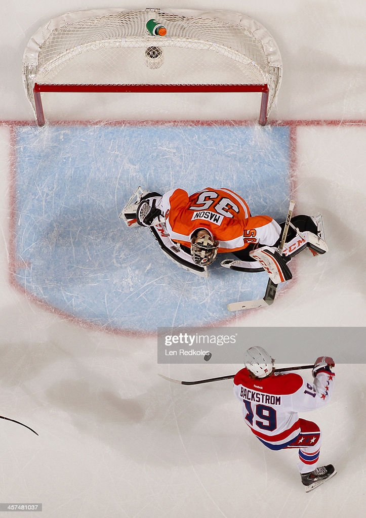 Nicklas Backstrom #19 of the Washington Capitals takes a shot on goaltender Steve Mason #35 of the Philadelphia Flyers on December 17, 2013 at the Wells Fargo Center in Philadelphia, Pennsylvania. The Flyers went on to defeat the Capitals 5-2.