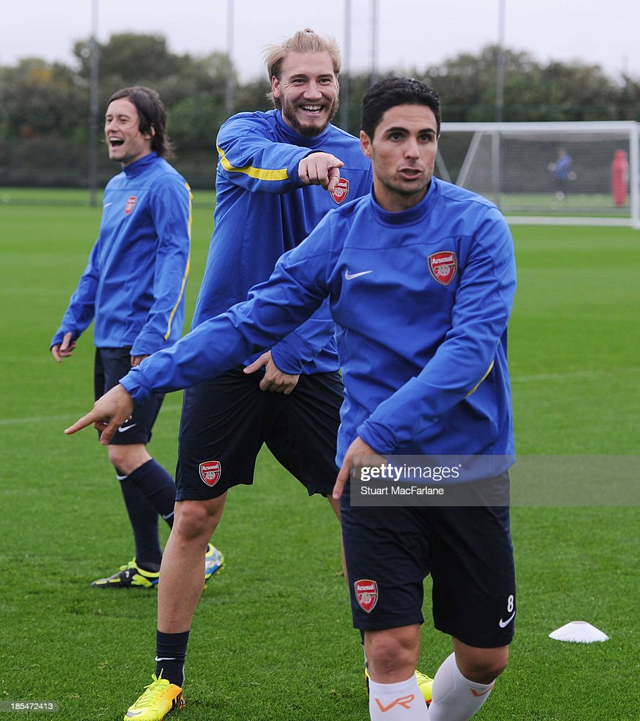 Nicklas Bendtner and Mikel Arteta of Arsenal during a training session at London Colney on October 21, 2013 in St Albans, England.
