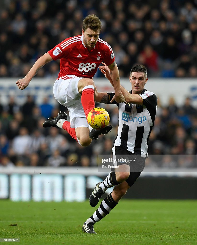 Nicklas Bendtner (l) challenges Ciaran Clark of Newcastle during the Sky Bet Championship match between Newcastle United and Nottingham Forest at St James' Park on December 30, 2016 in Newcastle upon Tyne, England.