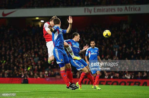 Nicklas Bendtner of Arsenal scores with a header during the Barclays Premier League match between Arsenal and Hull City at Emirates Stadium on...