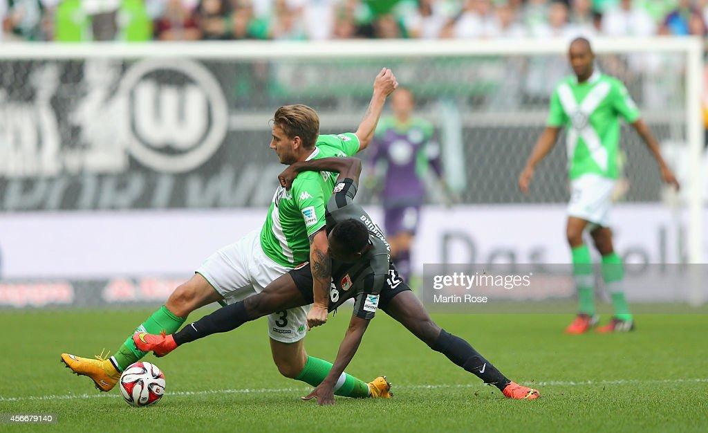 Nicklas Bendtner of Wolfsburg and Abdul Rahman Baba of Augsburg battle for the ball during the Bundesliga match between VfL Wolfsburg and FC Augsburg...