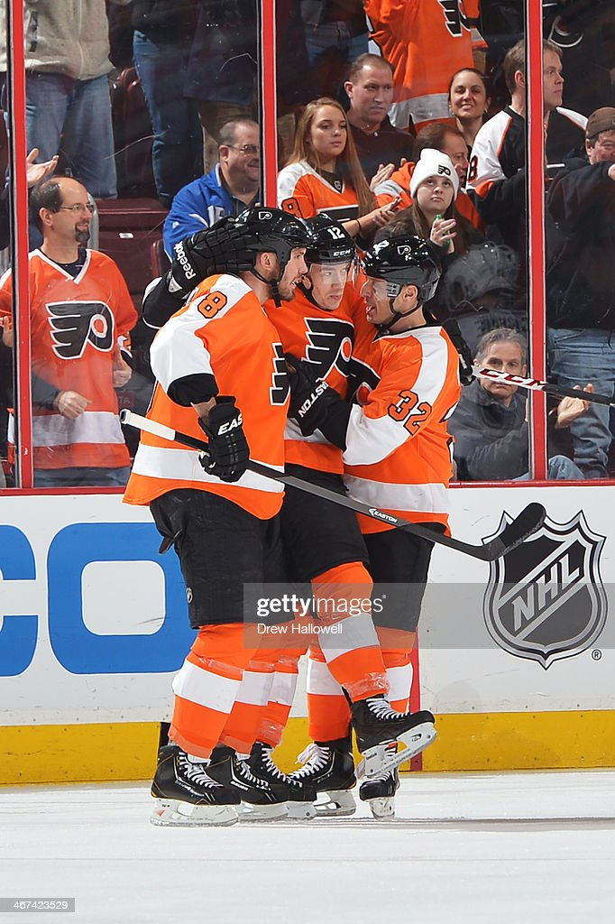 Nicklas Grossmann and Mark Streit of the Philadelphia Flyers congratulate teammate Michael Raffl on a second period goal against the Colorado...