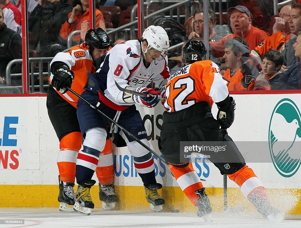 Nicklas Grossmann #8 and Simon Gagne #12 of the Philadelphia Flyers battle for the loose puck along the boards with Alex Ovechkin #8 of the Washington Capitals on February 27, 2013 at the Wells Fargo Center in Philadelphia, Pennsylvania. The Flyers went on to defeat the Capitals 4-1.