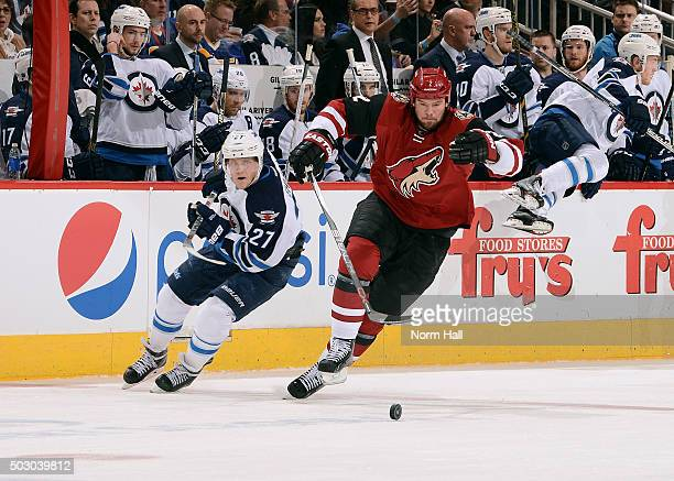 Nicklas Grossmann of the Arizona Coyotes skates for a loose puck ahead of Nikolaj Ehlers of the Winnipeg Jets during the first period at Gila River...