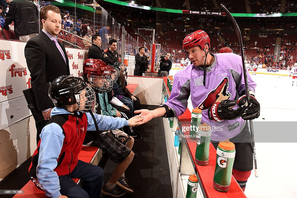 Nicklas Grossmann of the Arizona Coyotes wears a purple warmup in support of the NHL's leaguewide Hockey Fights Cancer initiative as he greets youth...