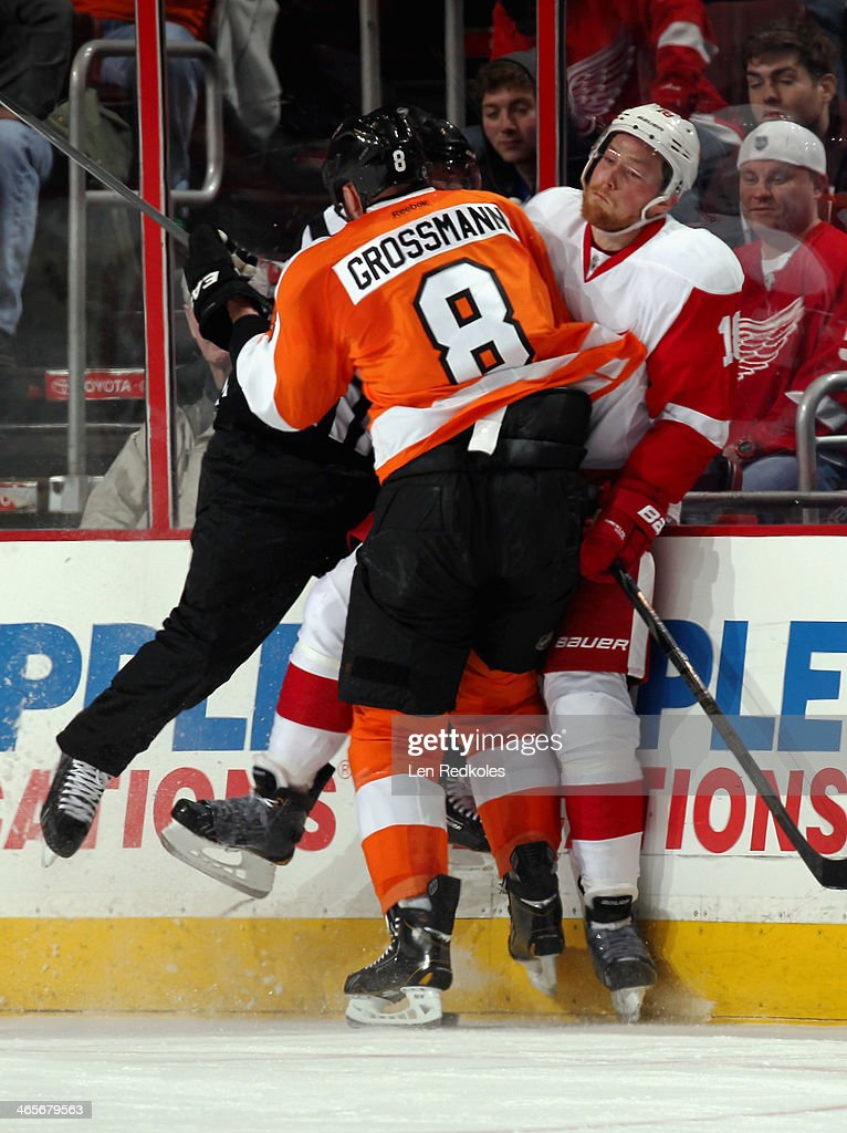 Nicklas Grossmann of the Philadelphia Flyers checks Joakim Andersson of the Detroit Red Wings and a member of the NHL officiating crew into the...