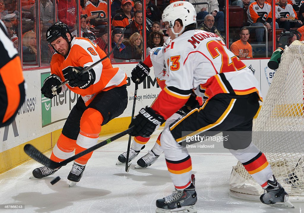 Nicklas Grossmann of the Philadelphia Flyers clears the puck away from Sean Monahan of the Calgary Flames at the Wells Fargo Center on February 8...